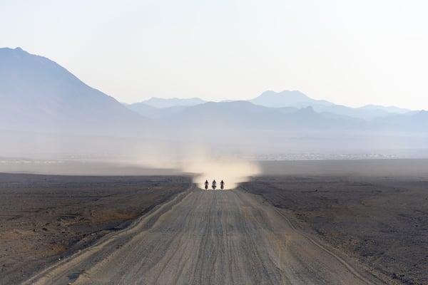 3 2020 Honda Africa Twins riding through the desert leaving dust in their wake.