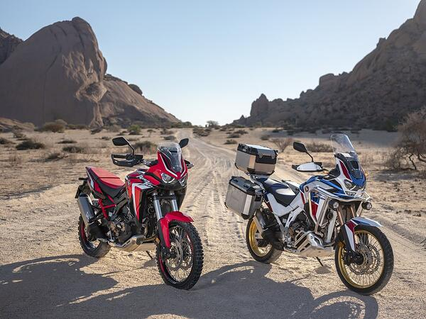 A Honda Africa Twin Standard model and Adventure Sports side by side in the desert.