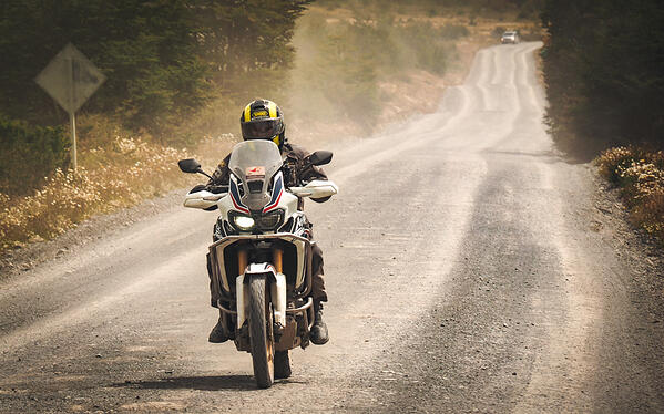 Rider in Patagonia on a Honda Africa Twin blazing down a gravel road.