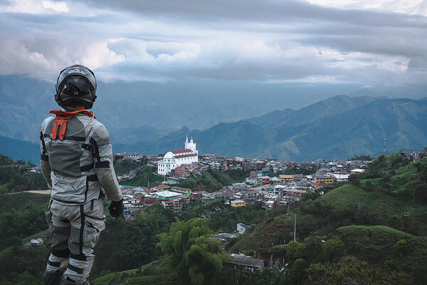 Full motorcycle gear Ricardo overlooking the Andes with a small church on one of the hills