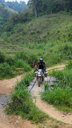 ADV Motorcycle riding across a bamboo bridge in Thailand in the jungle