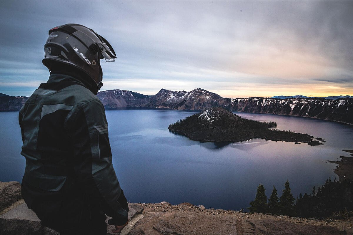 Motorcycle rider stopped at a viewpoint of Wizard Island at Crater Lake National Park.