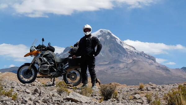 Eric posing with his bike in front of a massive volcano mountain
