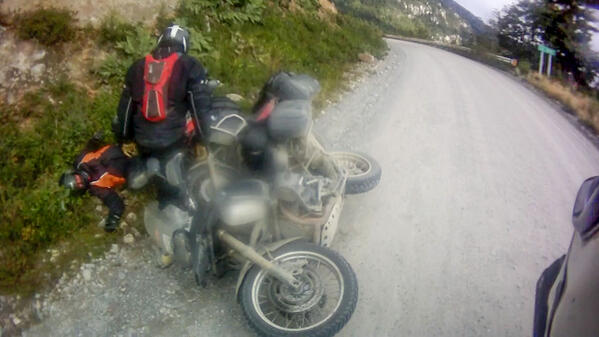A few guys on our adventure motorcycle tour in Bolivia get pinned by their hard motorcycle cases after crashing