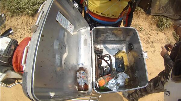 An opened hard motorcycle case with all of it's insides shaken and in scattered