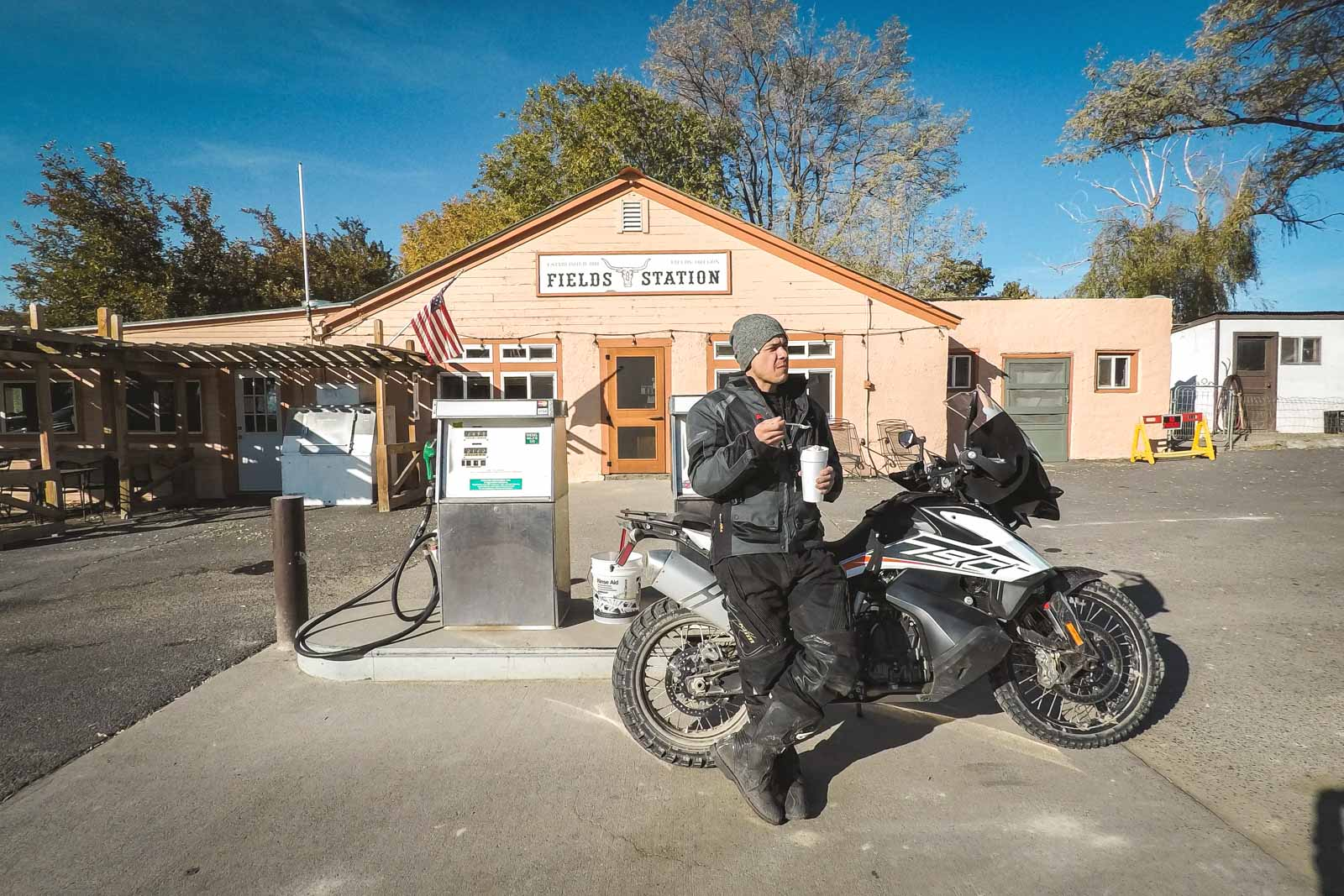 Garrett eating ice cream while leaning on the KTM 790 Adventure in front of fields station gas station